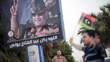 Ein Mann schwenkt die Flagge der libyschen Aufständigen vor einem Plakat des ermordeten General Junes.