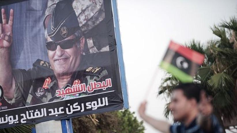 Krieg in Libyen: Ein Mann schwenkt die Flagge der libyschen Aufständigen vor einem Plakat des ermordeten General Junes.