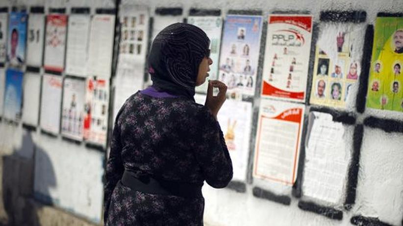 Tunesien: Eine Frau begutachtet Wahlplakate in der tunesischen Hauptstadt Tunis.