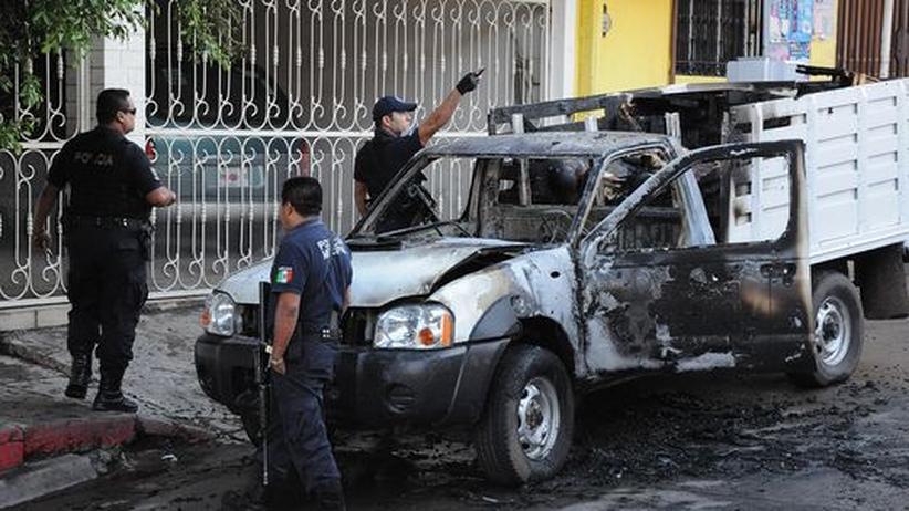 Kriminalität: Tote im Drogenkrieg: Forensiker der mexikanischen Polizei untersuchen ein Fahrzeug, in dem die Insassen verbrannten.