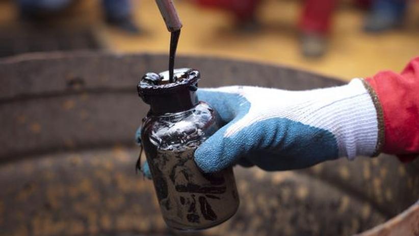 Energiepolitik: In Venezuela sammelt ein Arbeiter Rohöl-Proben