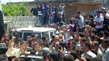 Bewohner von Hula umringen eine Gruppe von UN-Beobachtern in der Stadt, in der mehr als 100 Menschen getötet worden waren.