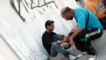 In Thessaloniki nehmen zwei Männer ein Essen der Wohlfahrt zu sich.