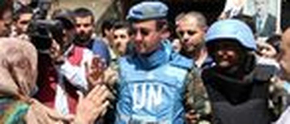 Anhänger von Präsident Assad sprechen mit UN-Blauhelmen.
