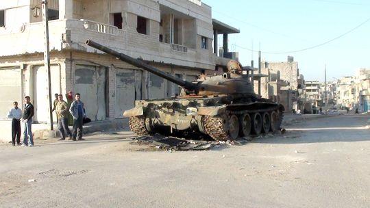 Syrer neben einem zerstörten Panzer in der Stadt Rastan (Archiv)