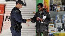 Ein Polizist überprüft die Papiere eines Migranten in Athen.