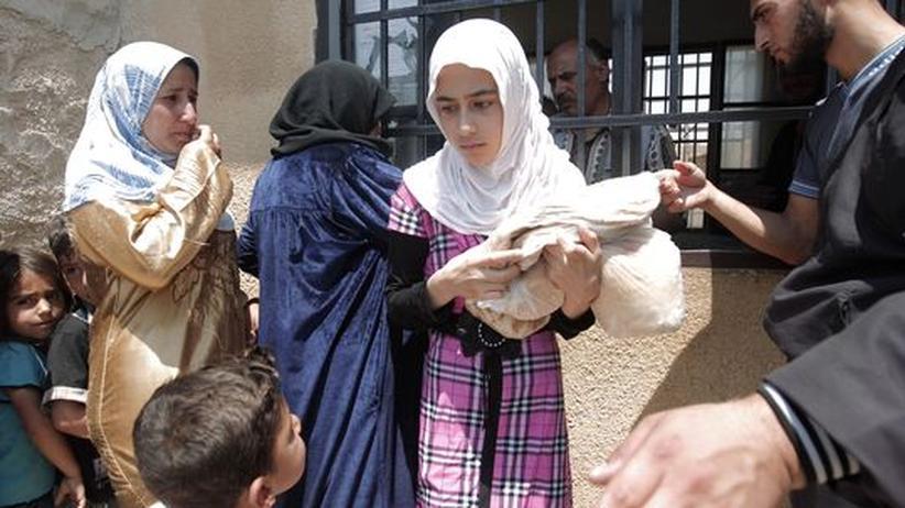 Ein syrisches Mädchen trägt eine Tasche mit Brot.