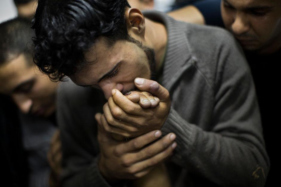 Dutzende Palästinenser sind durch Angriffe der israelischen Armee ums Leben gekommen: Hier küsst ein Mann in einem Krankenhaus in Gaza-Stadt die Hand eines toten Angehörigen.