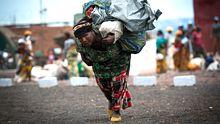 Eine Binnenvertriebene trägt ihre Sachen in ein UN-Lager in der Nähe der kongolesischen Stadt Goma.