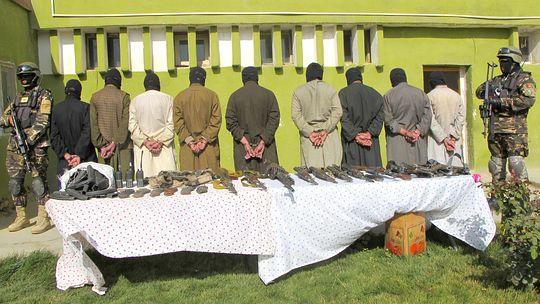 Festgenommene Taliban in Afghanistan, im Vordergrund ihre Waffen