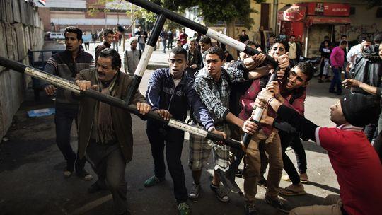 Gegner des ägyptischen Präsidenten Mursi beseitigen die Absperrungen vor dem Palast in Kairo.