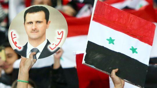 Eine Anhängerin von Syriens Präsidenten Baschar al-Assad zeigt sein Porträt im Fußballstadion von Kuwait City.