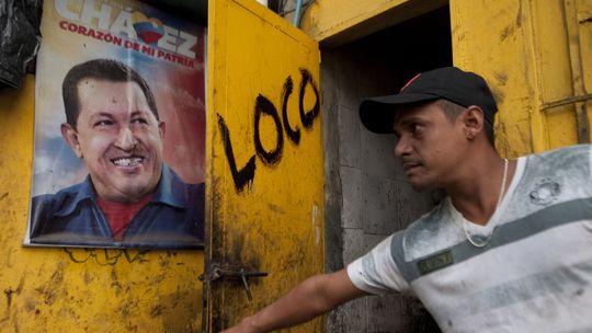 Ein Bewohner von Caracas betrachtet ein Poster des venezolanischen Präsidenten Hugo Chávez (Archiv)