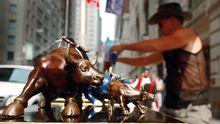 Ein Mann in New York verkauft den Börsenbulle vor der New Yorker Wall Street als Touristensouvenier.
