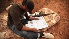 Ein Kämpfer der Rebellen liest nahe der libyschen Stadt Misrata eine Zeitung.