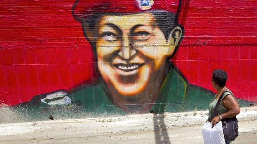 Eine Frau vor einem Chávez-Graffito in Caracas