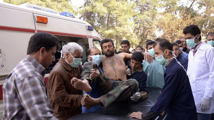 Rettungskräfte heben einen verletzten syrischen Soldaten auf eine Trage.