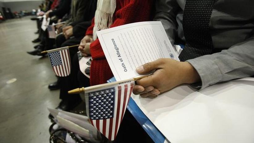 US-Einwanderungspolitik: Einwanderer halten die US-Fahne während einer Einbürgerungszeremonie in Los Angeles in den Händen.