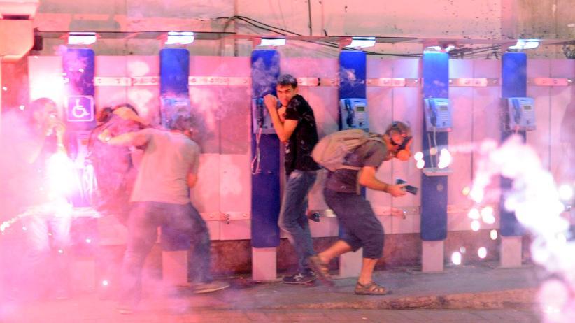 Polizeieinsätze: Demonstranten in Istanbul suchen Schutz vor Tränengasgranaten.