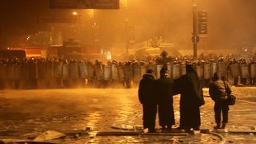 Priester zwischen Demonstranten und Polizei