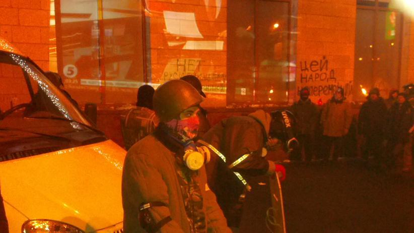 Demonstranten folgen einer TV-Übertragung auf einer Häuserwand in der Gruschewski-Straße.