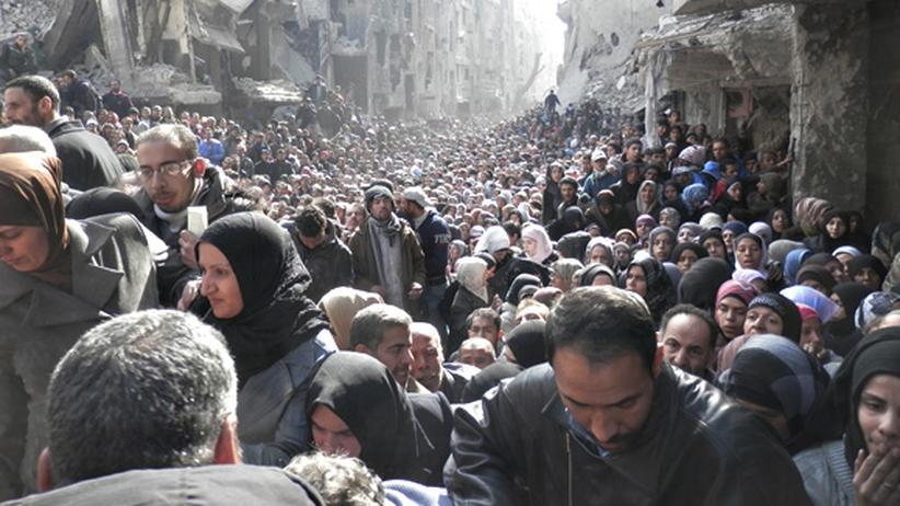 Syrien: Eine nicht enden wollende Menge von Kindern, Frauen und Männern wartet in Yarmouk,  einem zerbombten Stadtteil im Süden von Damaskus, auf Nahrung und Medizin.