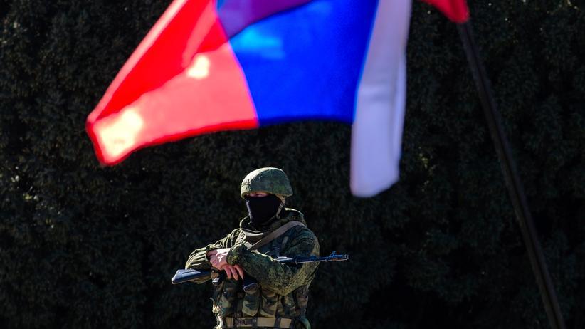 Ein schwerbewaffneter Soldat unter einer russischen Flagge vor dem Sitz der Regionalregierung der Krim in Simferopol