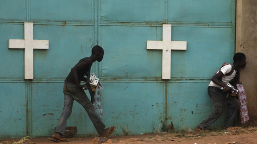 Menschen suchen bei einer Kirche Schutz vor Schüssen zwischen afrikanischen Friedenstruppen und christlichen Milizen.