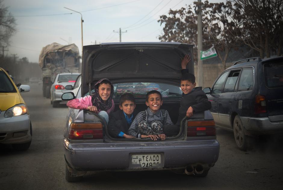 Kinder im Kofferraum eines Autos auf der Straße in Kabul