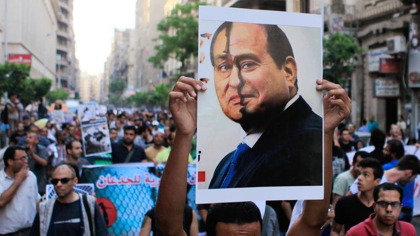 Ein Demonstrant mit einer Abbildung des früheren Präsidenten Mubarak (links) und des aktuellen Kandidaten Abdel Fattah al-Sissi