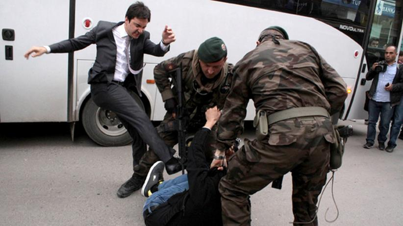 Erdoğan-Berater Yusuf Yerkel holt zum Tritt aus, während zwei Sicherheitskräfte einen Mann am Boden festhalten.