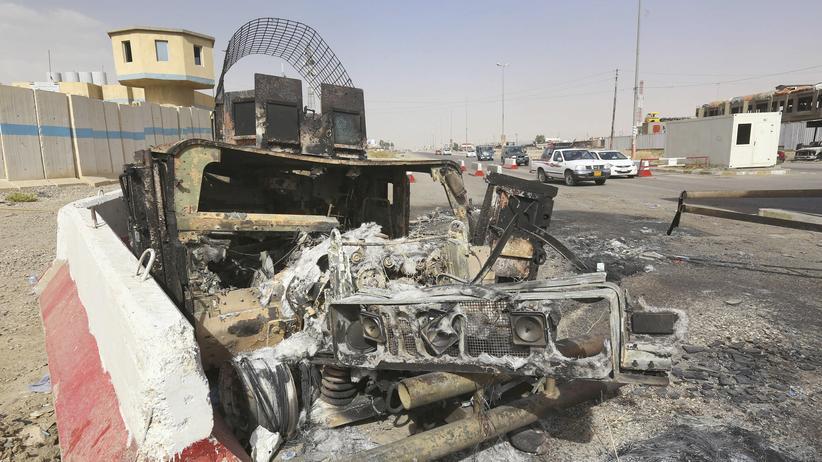 Irak: Am Checkpoint im Osten Mosuls steht ein ausgebranntes Fahrzeug