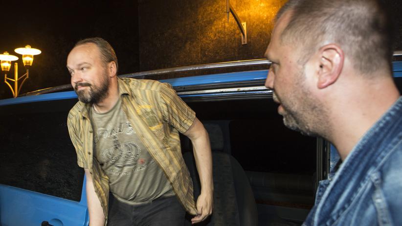 Ostukraine: Ein Mitglied des freigelassenen OSZE-Beobachterteams steigt am Donnerstagabend aus einem Fahrzeug. Neben ihm (rechts) steht der Anführer der prorussischen Separatisten Alexander Borodai.