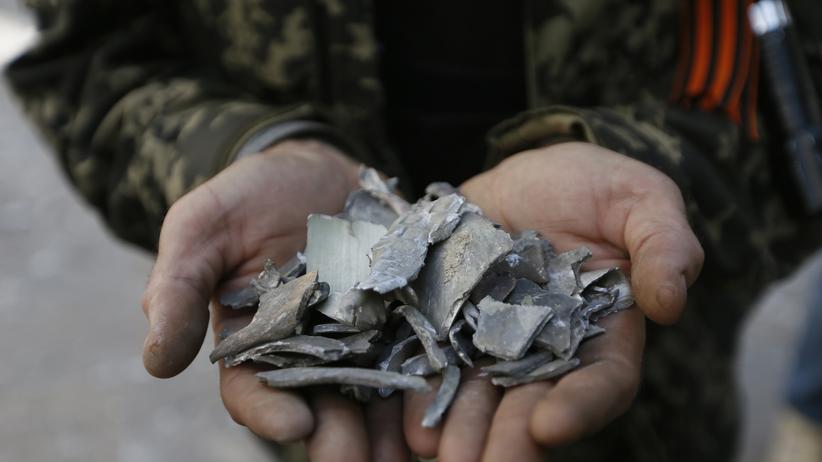Ein prorussischer Separatist zeigt Granatsplitter einer Explosion in der Stadt Luhansk.