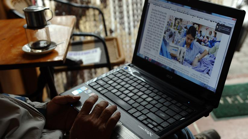 Vietnam: Ein Mann liest Nachrichten auf seinem Laptop in einem Café in Hanoi.