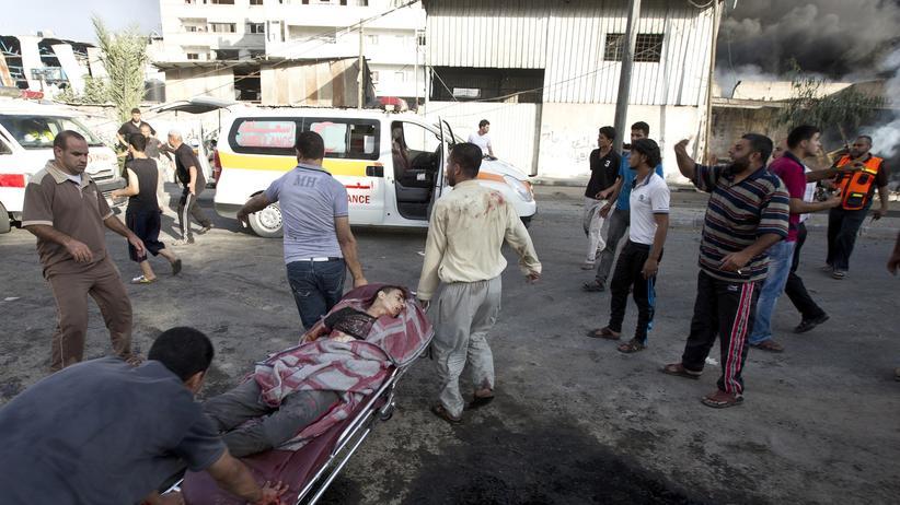 Nahost-Konflikt: Palästinenser transportieren nach einem Angriff auf einen Markt in Gaza einen Verletzten.