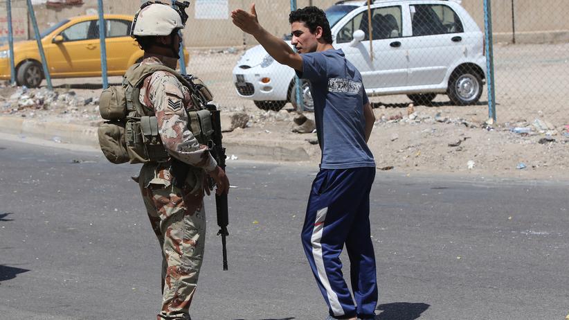 Irak: Iraker mit einem Bewaffneten in Bagdad (Archivbild)