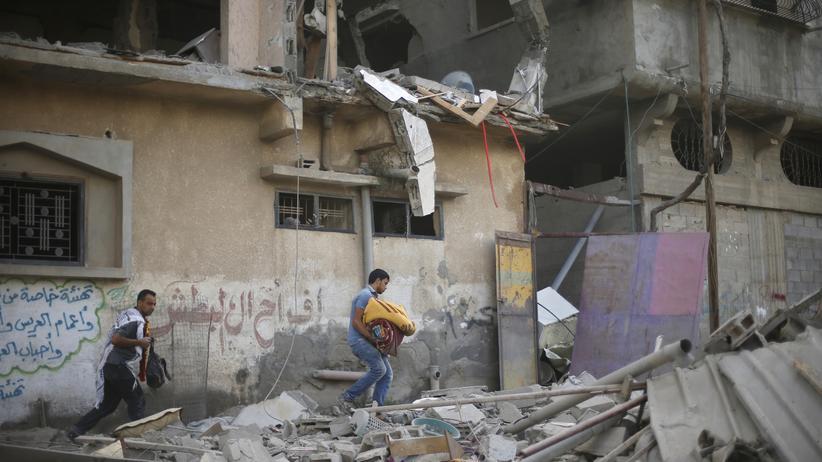 Palästinenser im Gazastreifen retten ihr Hab und Gut aus zerstörten Häusern.