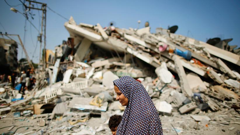 Gaza-Konflikt: Zivile Opfer: Eine Palästinenserin geht mit ihrem Kind an einem Haus in Gaza vorbei, das durch einen israelischen Angriff zerstört wurde.