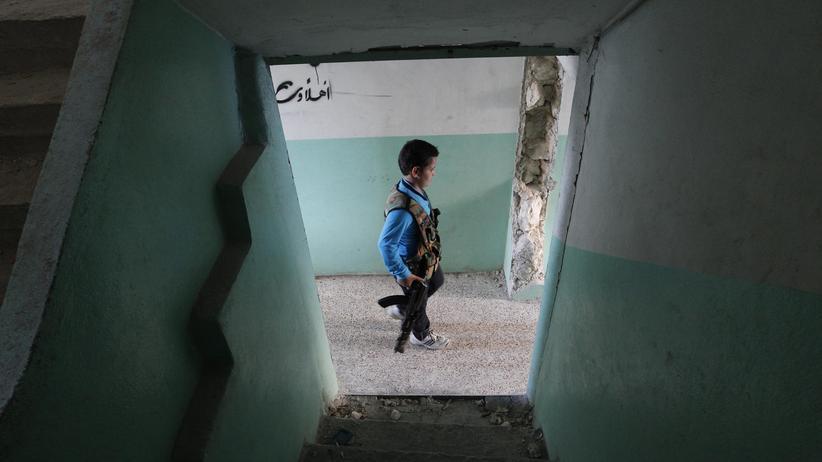 Menschenrechte: Ein 12-Jähriger mit einem Gewehr geht im syrischen Aleppo durch ein zerstörtes Haus (Archiv).