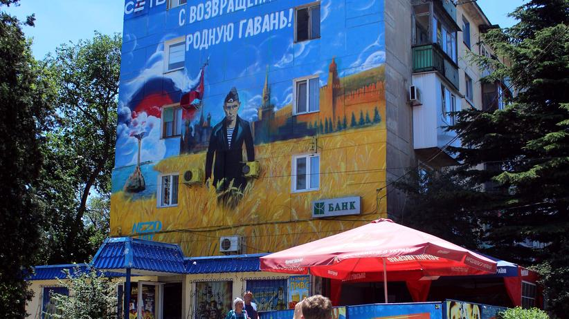 Krim: Pedestrians walk by a mural depicting Russian president Vladimir Putin dressed as a Russian Navy seaman, in the Crimean city of Sevastopol on June 28, 2014. Russian President Vladimir Putin said on June 27, 2014 that Ukrainian society is split after being forced to choose between Europe and Russia, speaking shortly after Kiev inked the EU association accord.The inscription in Russian reads : 'Returning to their home harbour'. AFP PHOTO / YURI LASHOV (Photo credit should read YURI LASHOV/AFP/Getty Images)
