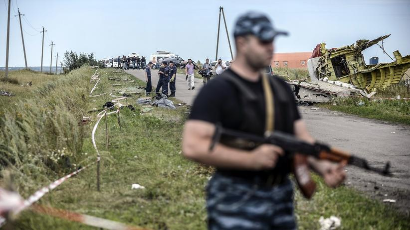 MH17: Bewaffnete prorussische Separatisten vor Flugzeugteilen des Fluges MH17
