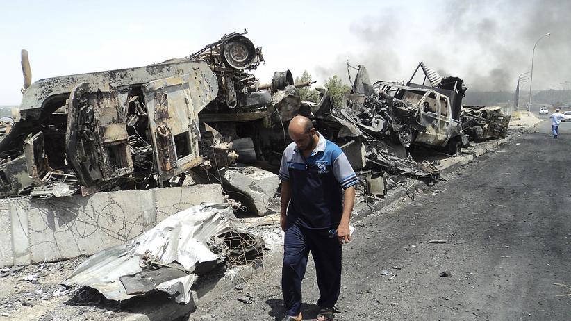 Irak: Ein Mann läuft in Mossul an zerstörten Armeefahrzeugen vorbei.