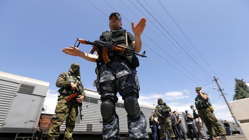 Prorussische Separatisten vor Kühlwaggons, in denen die Toten des abgestürzten Flugzeugs transportiert werden