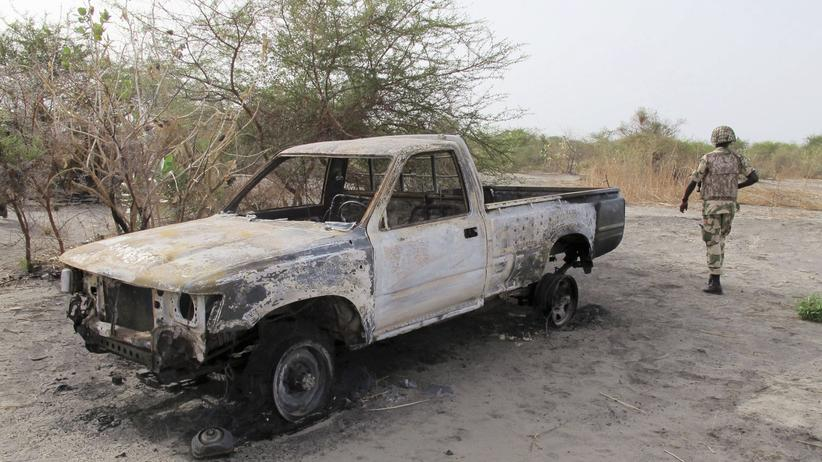 Nigeria: Ein nigerianischer Soldat geht in Maiduguri an einem bei einem Boko Haram Angriff ausgebrannten Auto vorbei.
