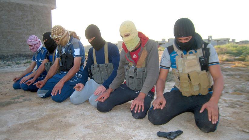 Islamischer Staat: Bewaffnete und maskierte Mitglieder der sunnitischen Terrorgruppe IS bei einem Gebet außerhalb der irakischen Stadt Falluja (Archivbild, April 2014)