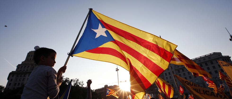 Ein Junge schwenkt die Flagge der Katalanen.