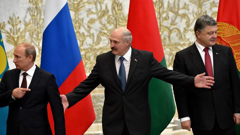 Ukraine-Krise: Weißrusslands Präsident Alexander Lukaschenko (Mitte) weist den russischen Präsidenten Wladimir Putin (links) und den ukrainischen Präsidenten Petro Poroschenko ein.