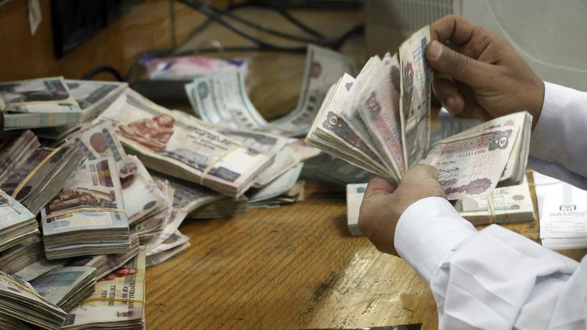 Ein Angestellter zählt Geld in einer Bank in Kairo (Archiv).