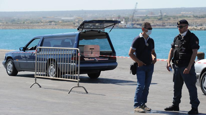 Polizisten auf Sizilien neben einem Leichenwagen mit dem Sarg eines getöteten Migranten